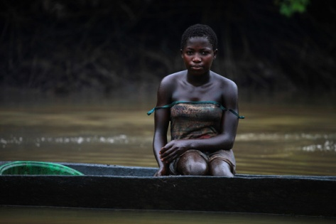 A young woman named Akpomene is pictured coated in oil stains as she sits in a canoe near river Nun