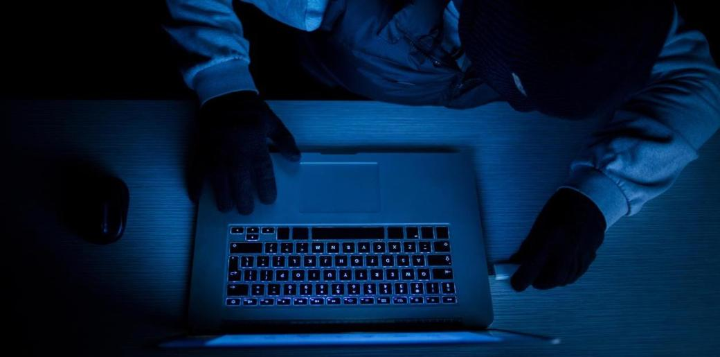 Hacker thief with laptop in darkness